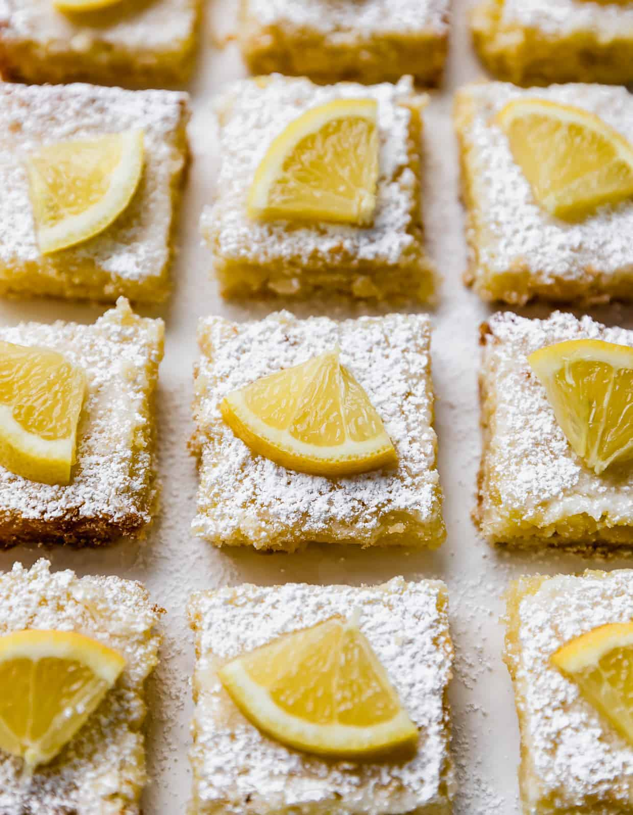 Lemon bars lined up next to one another, each topped with powdered sugar and a fresh slice of lemon.