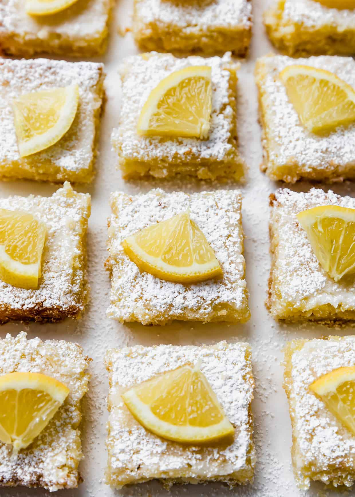 Lemon bars topped with powdered sugar and a wedge of fresh lemon.