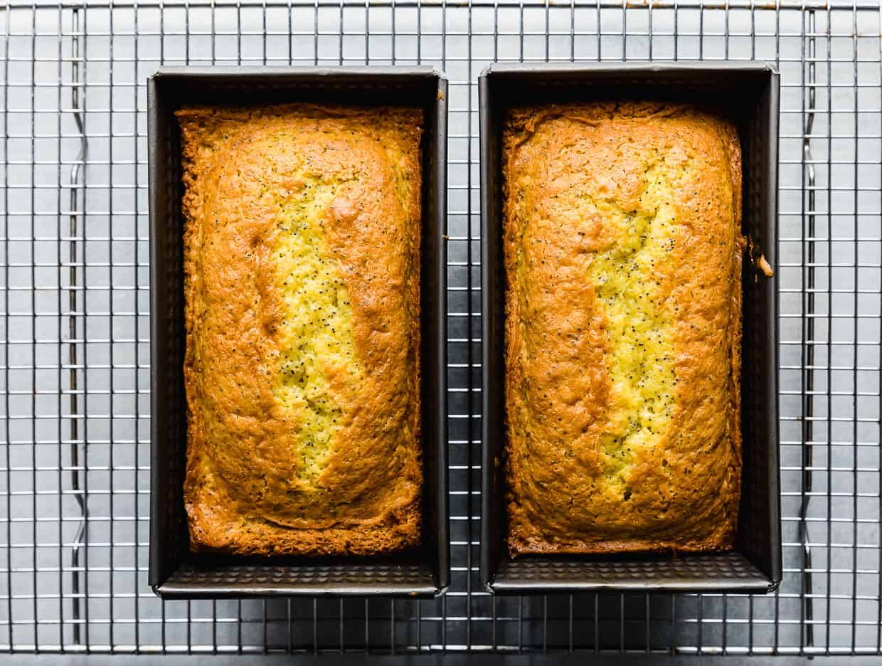 Two loaf pans on a wire cooling rack, each loaf pan has a golden brown freshly baked lemon poppy seed loaf in it.