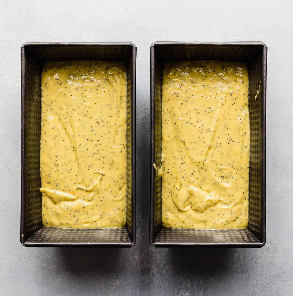 Two loaf pans full of lemon poppy seed bread batter.