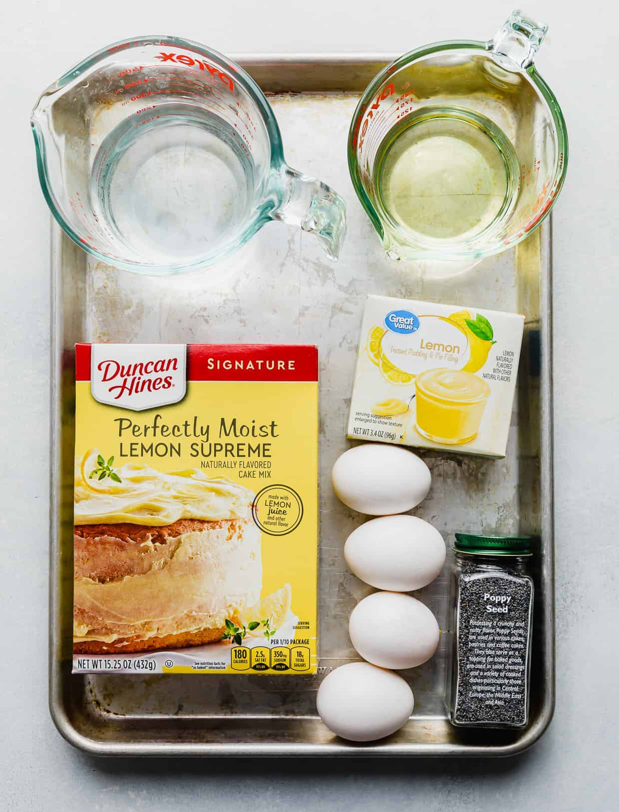 Ingredients used to make lemon bread on a baking sheet: lemon cake mix, water, oil, eggs, lemon pudding mix, and poppy seeds.