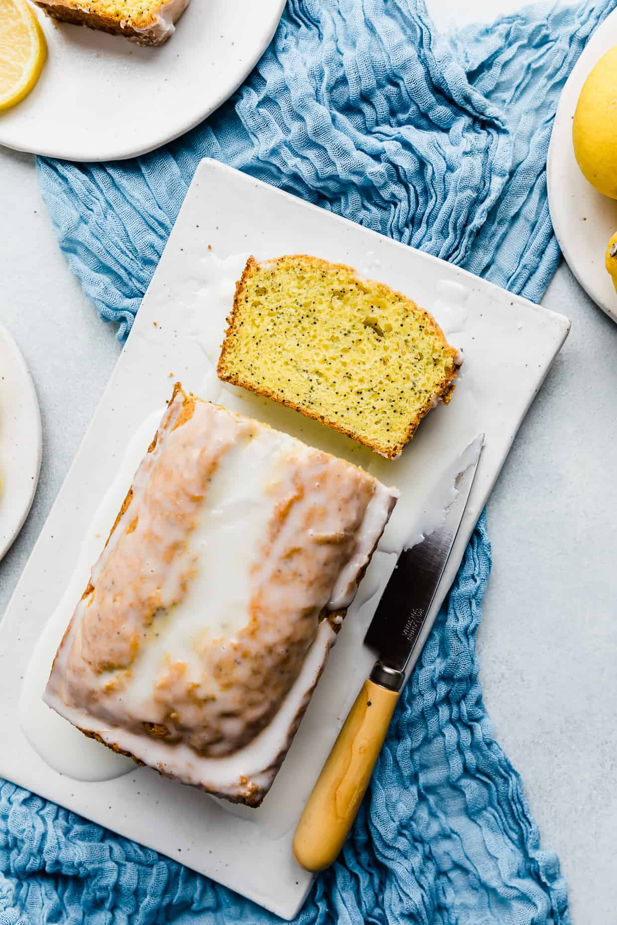 Overhead photo of Lemon Poppy Seed Bread on a white rectangle plate resting on a blue cloth.
