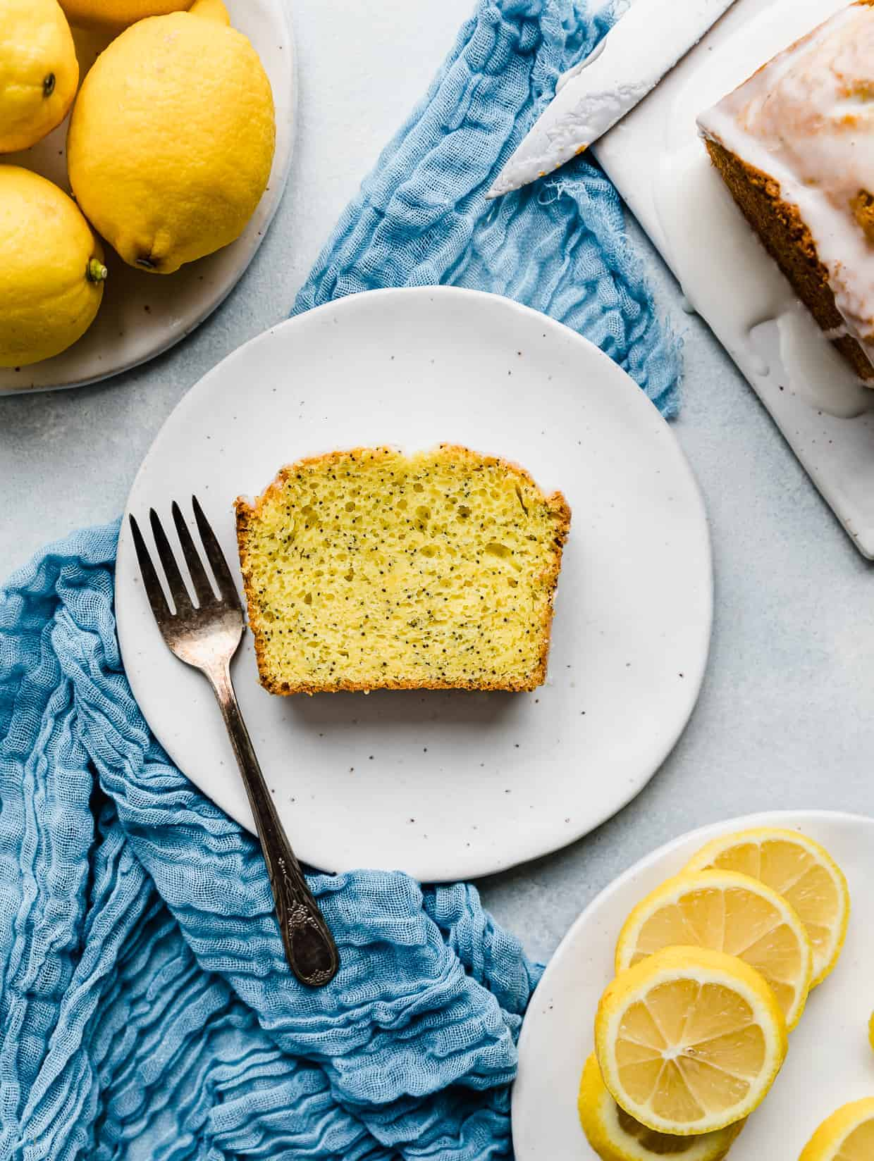 A slice of lemon poppy seed bread on a white plate with a fork next to the slice.