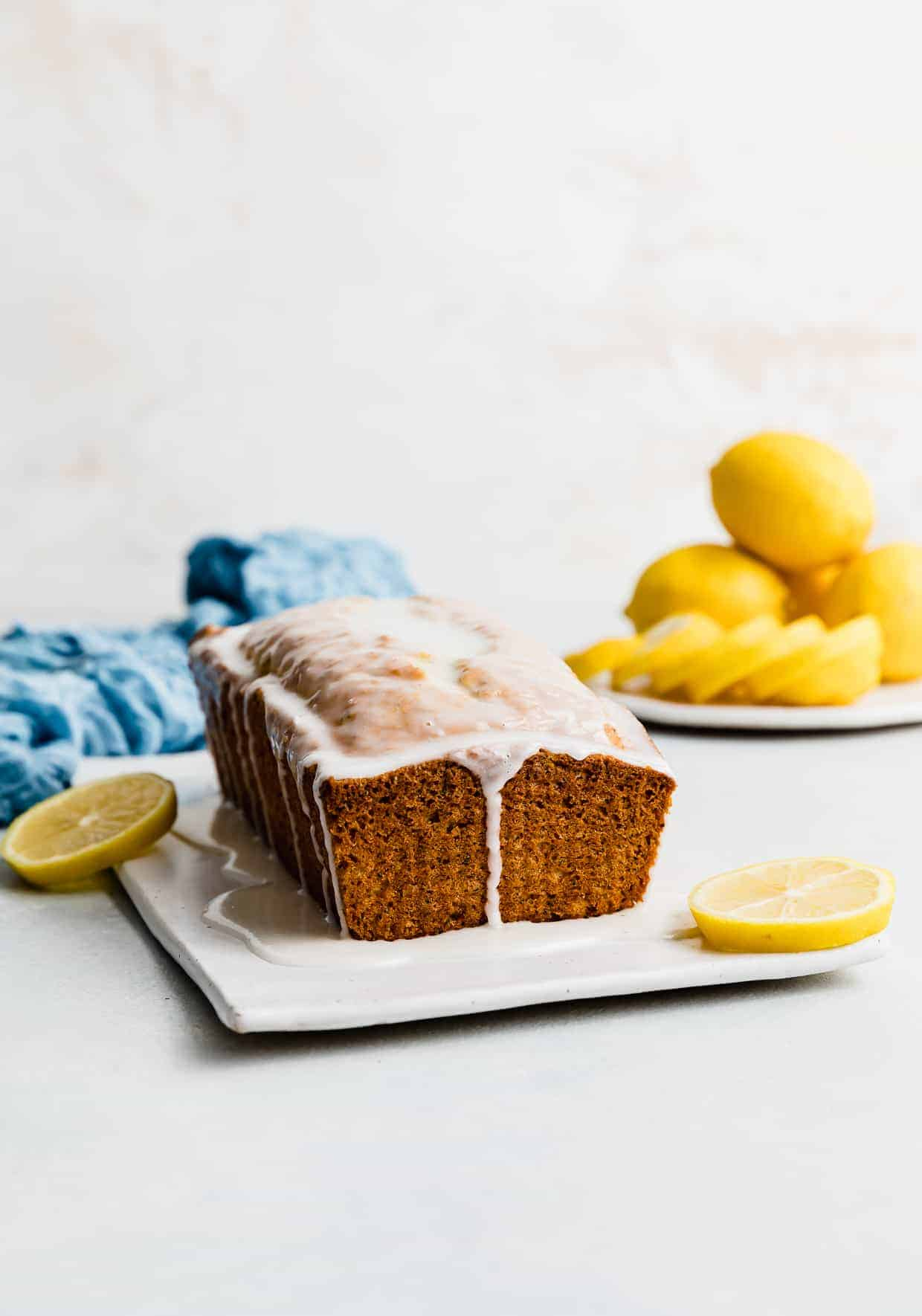 A loaf of Lemon Poppy Seed Bread drizzled with a white glaze against a white background, with yellow lemons stacked on a plate near the loaf.