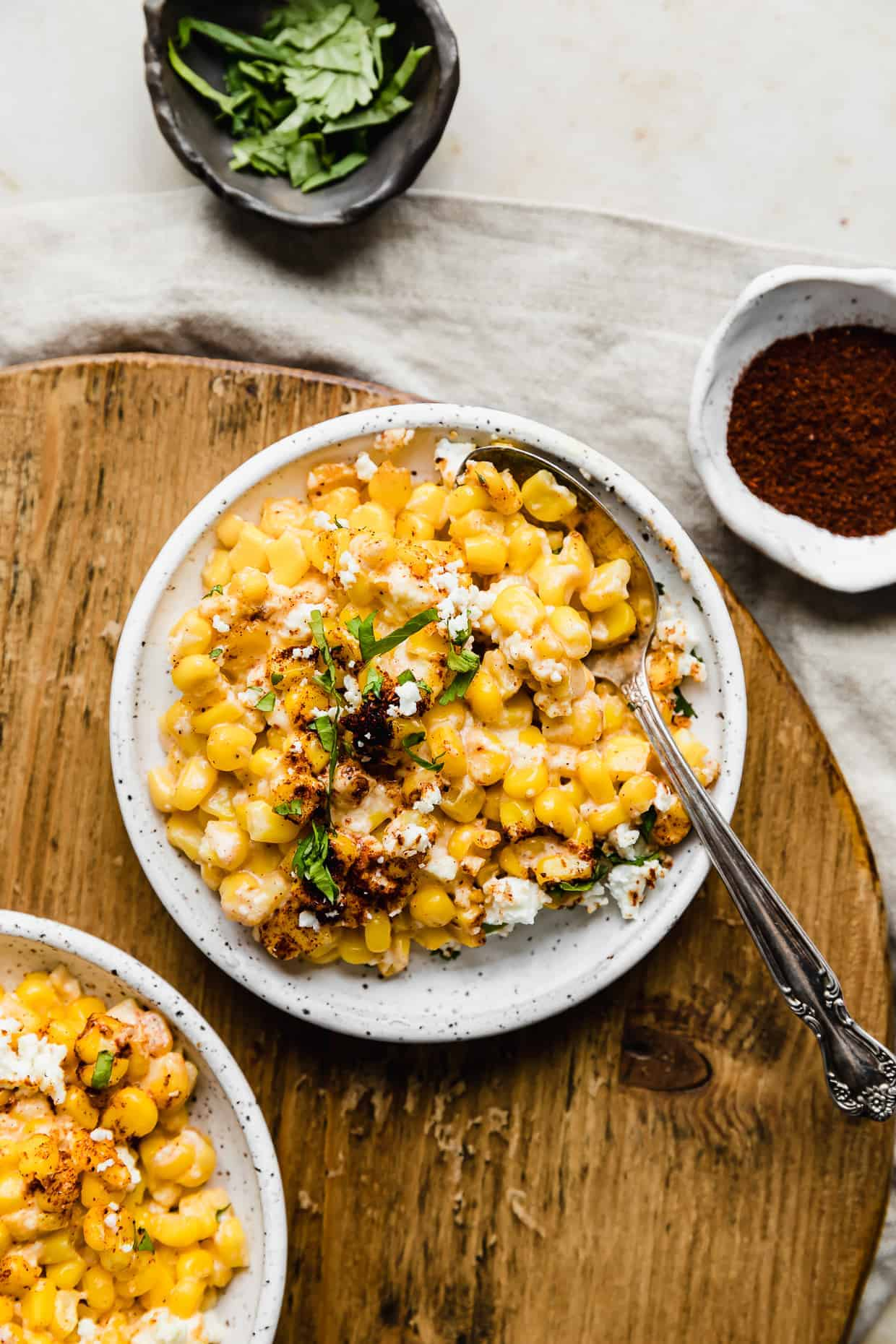 Mexican Street Corn kernels garnished with cilantro and chili powder on a white plate against a wooden cutting board.