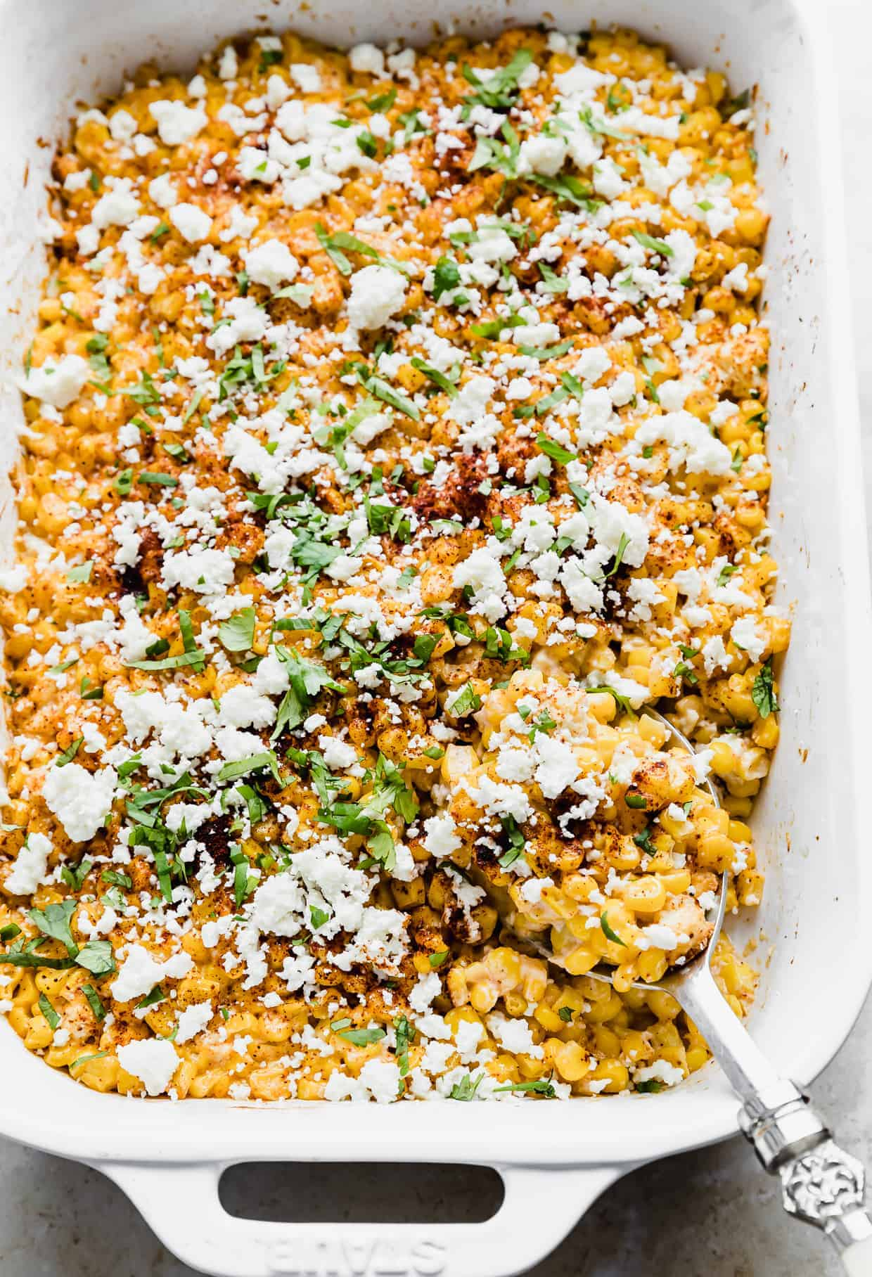 A spoon scooping into a casserole dish that is full of cilantro and chili powder covered corn kernels.