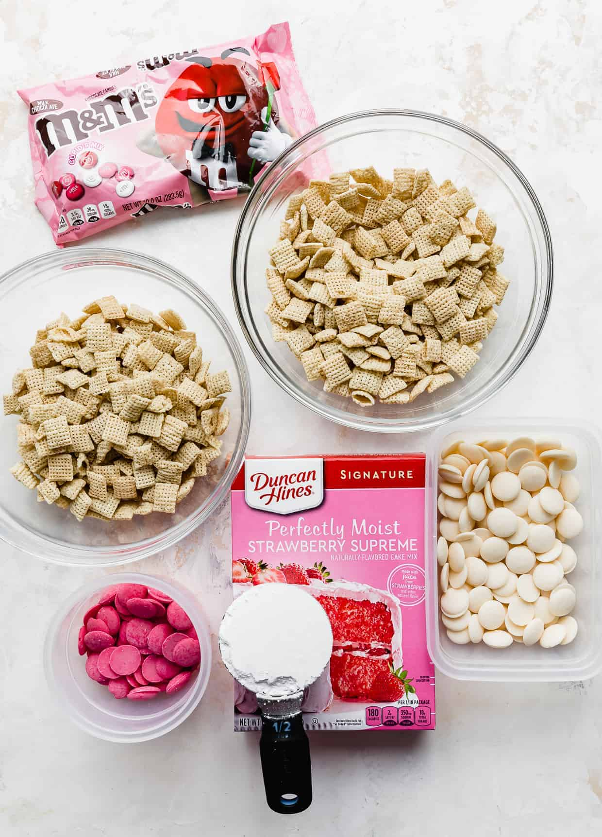 Rice Chex mix, strawberry cake mix box, powdered sugar, Valentine's Day M&M's, and white and pink candy melts against a white background.