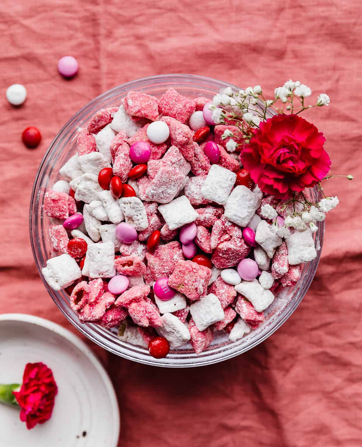 A bowl of white and pink muddy buddies and M&M's against a pink background.