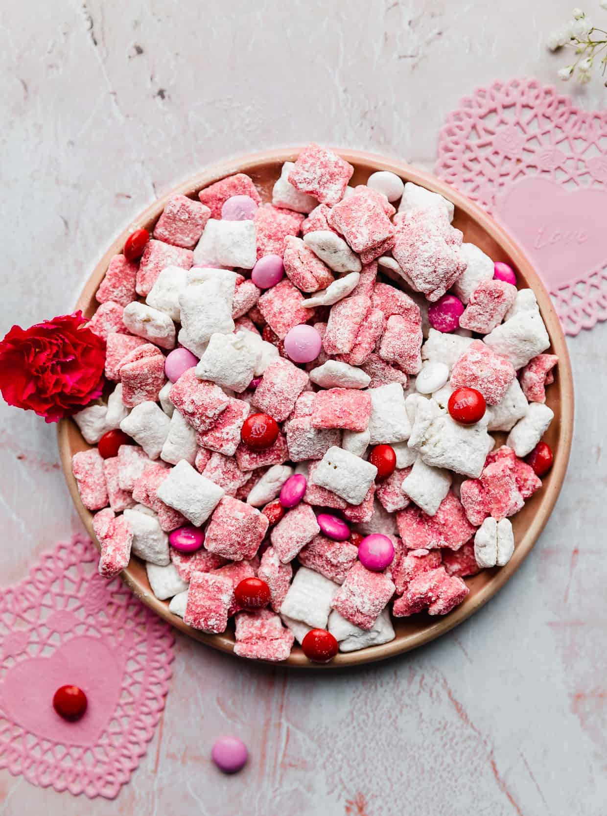 A plate of white and pink colored muddy buddies tossed with pink, red, and white M&M candy.