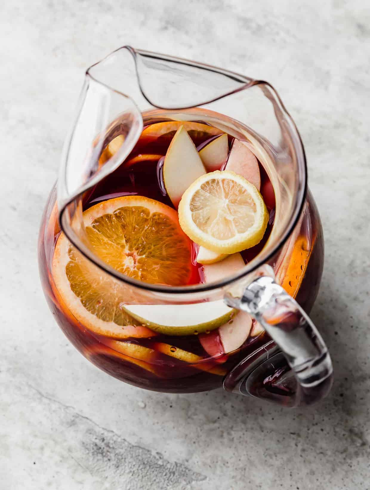 A virgin sangria drink in a glass pitcher with slices of fresh oranges, apples, lemons, and pears floating in the drink.