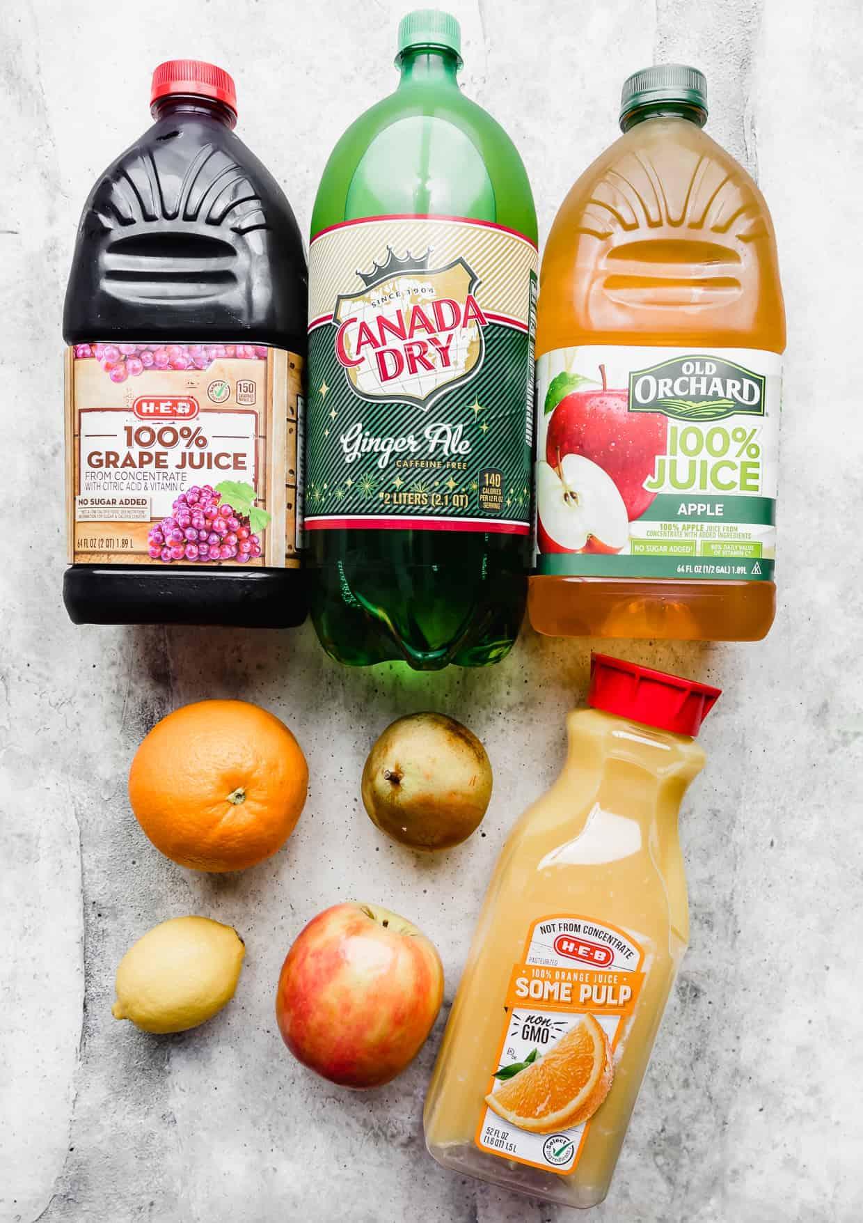 Bottles of ginger-ale, grape juice, orange juice, apple juice laying on a gray background.