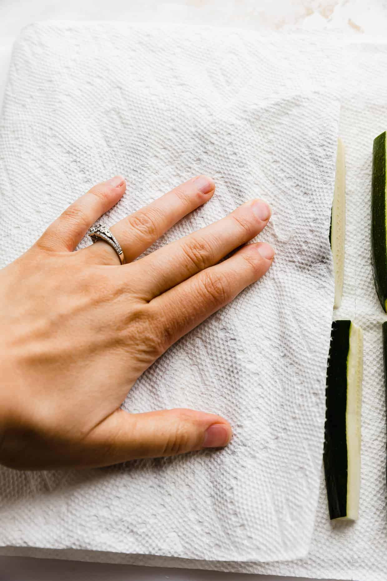 A hand pressing a white paper towel onto zucchini fries.