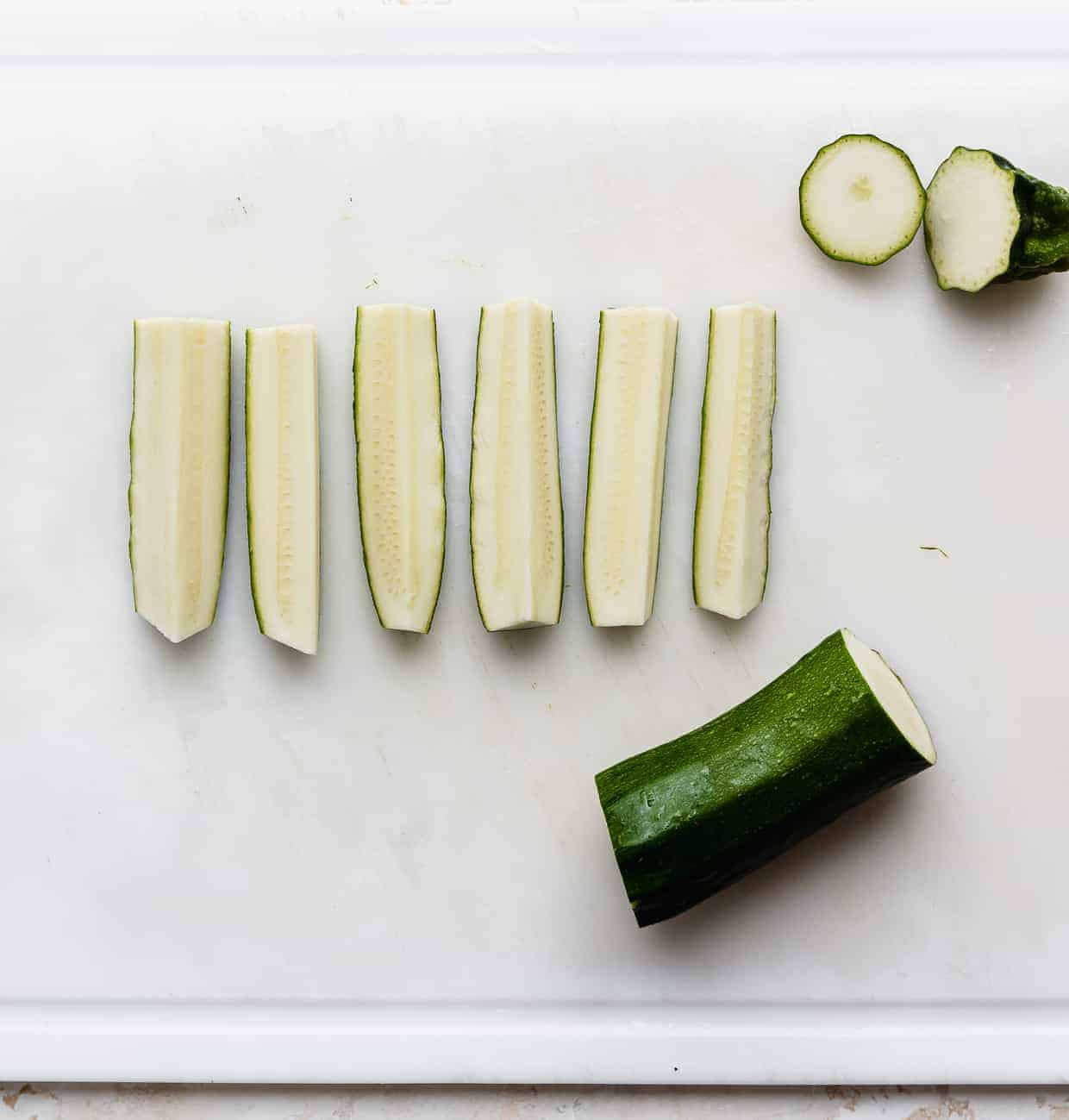 Freshly cut zucchini strips on a white cutting board, to make baked zucchini fries.