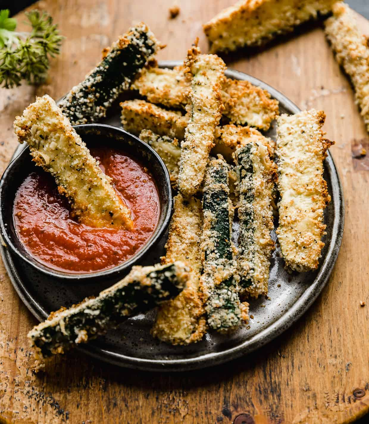 Zucchini fries on a black plate against a wooden background, with one zucchini fry dipped into pizza sauce.