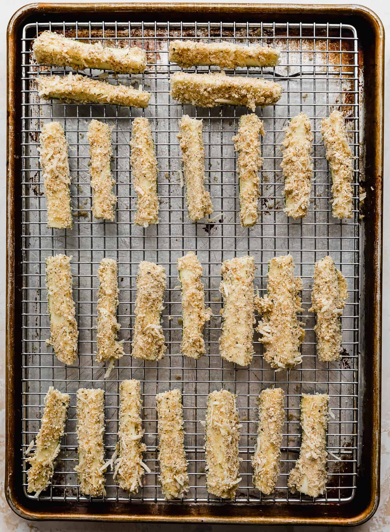 Raw zucchini fries lined up on a wire rack lined baking sheet.