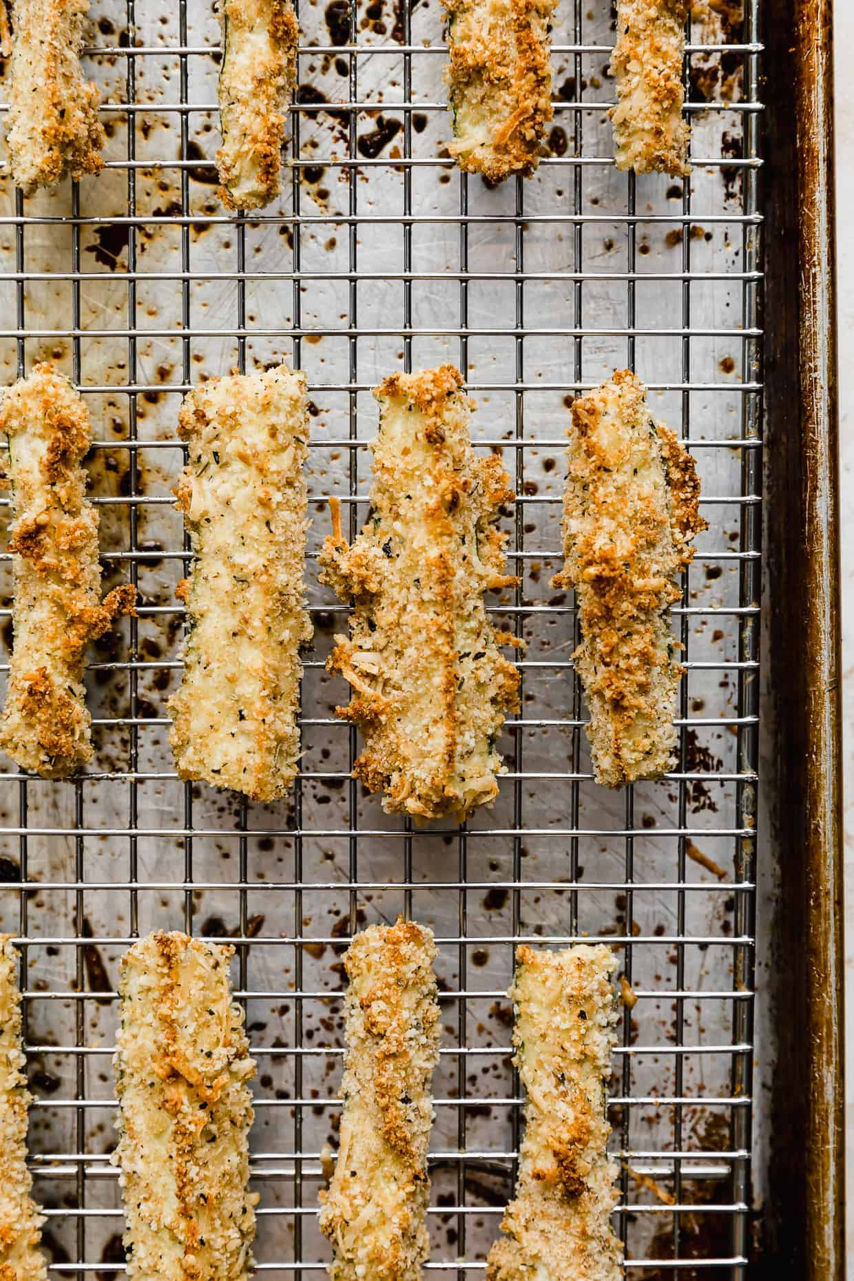Close up photo of lightly browned crispy baked zucchini fries on a wire rack.