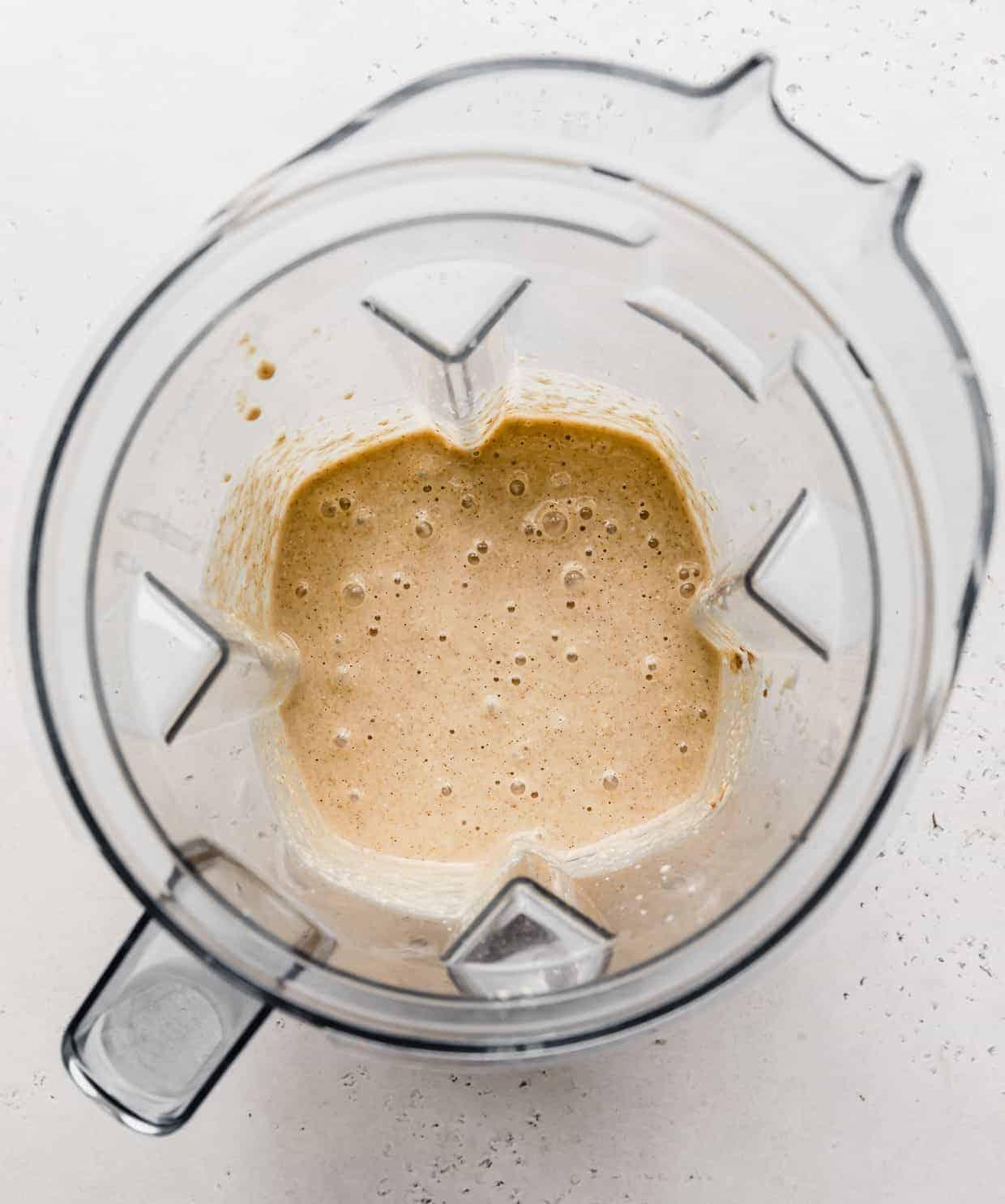 Banana Oatmeal Pancake batter in a blender against a light gray background.