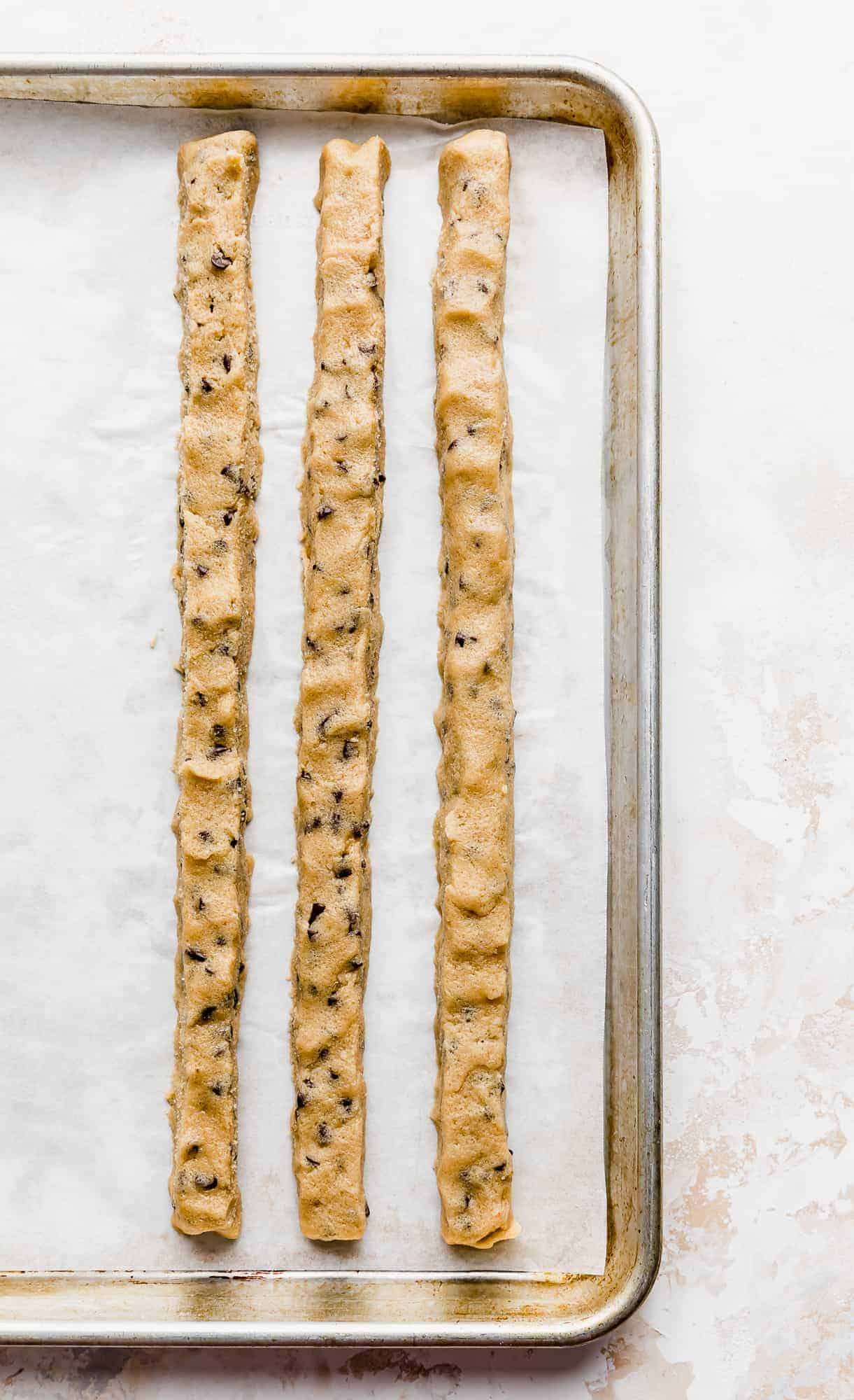 3 ropes of edible cookie dough on a baking sheet against a white background.