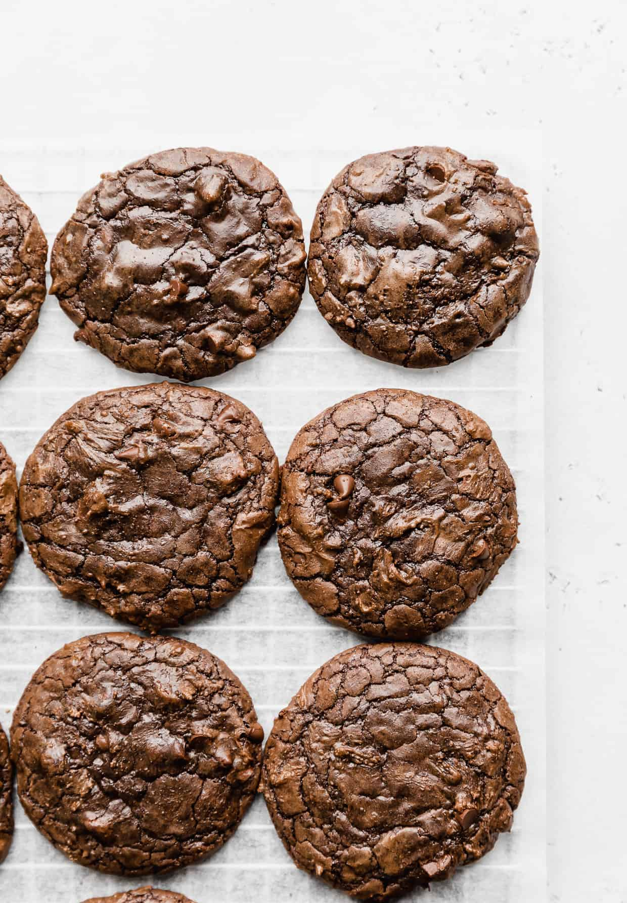Crackly top brownie mix cookies against a white parchment background.