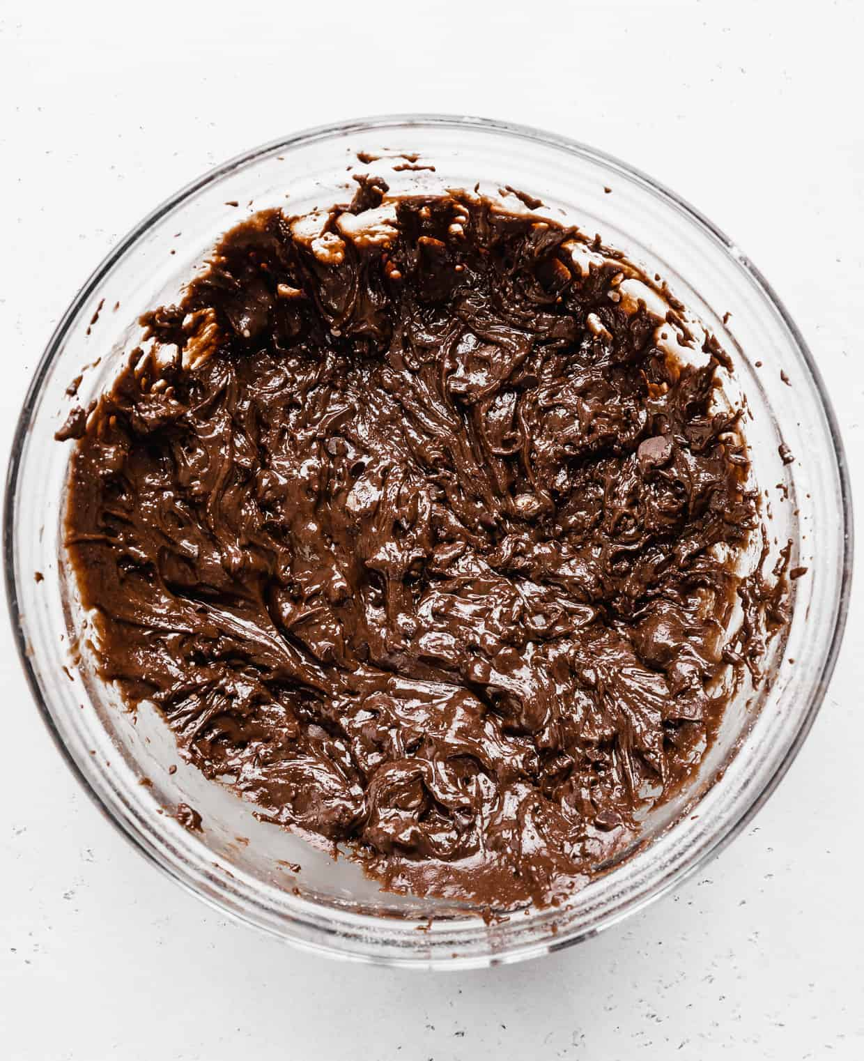 A glass bowl full of brownie cookie batter studded with chocolate chips.