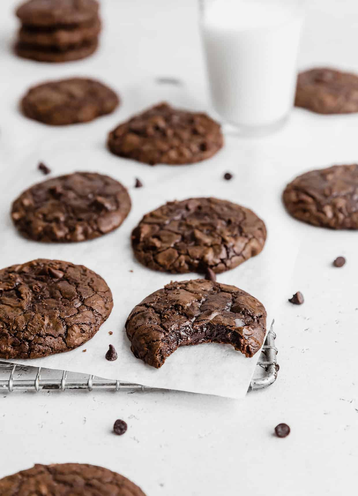 Brownie mix cookies sitting on a wire rack that is covered with white parchment paper.