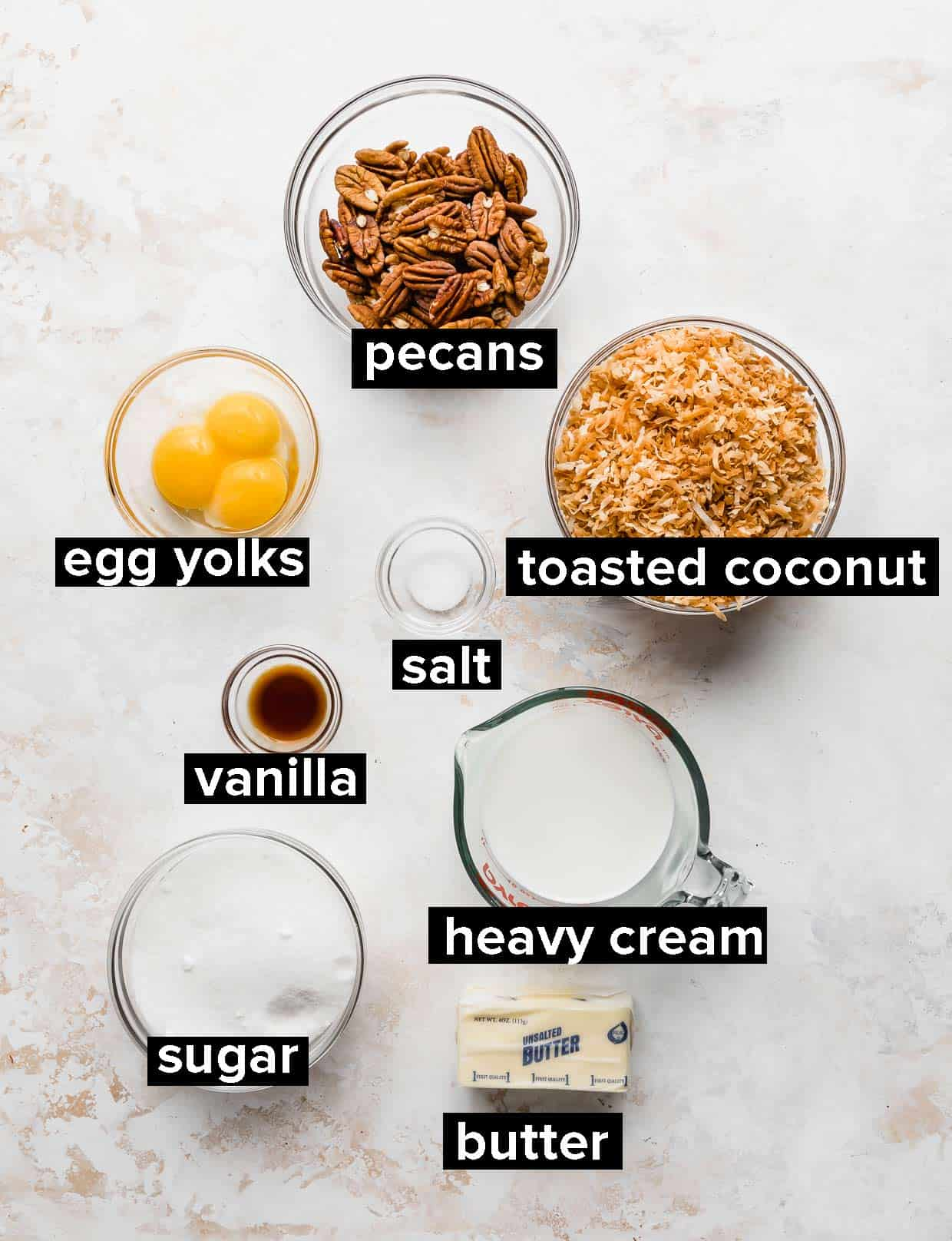 Ingredients used to make coconut pecan frosting, on a white textured background.