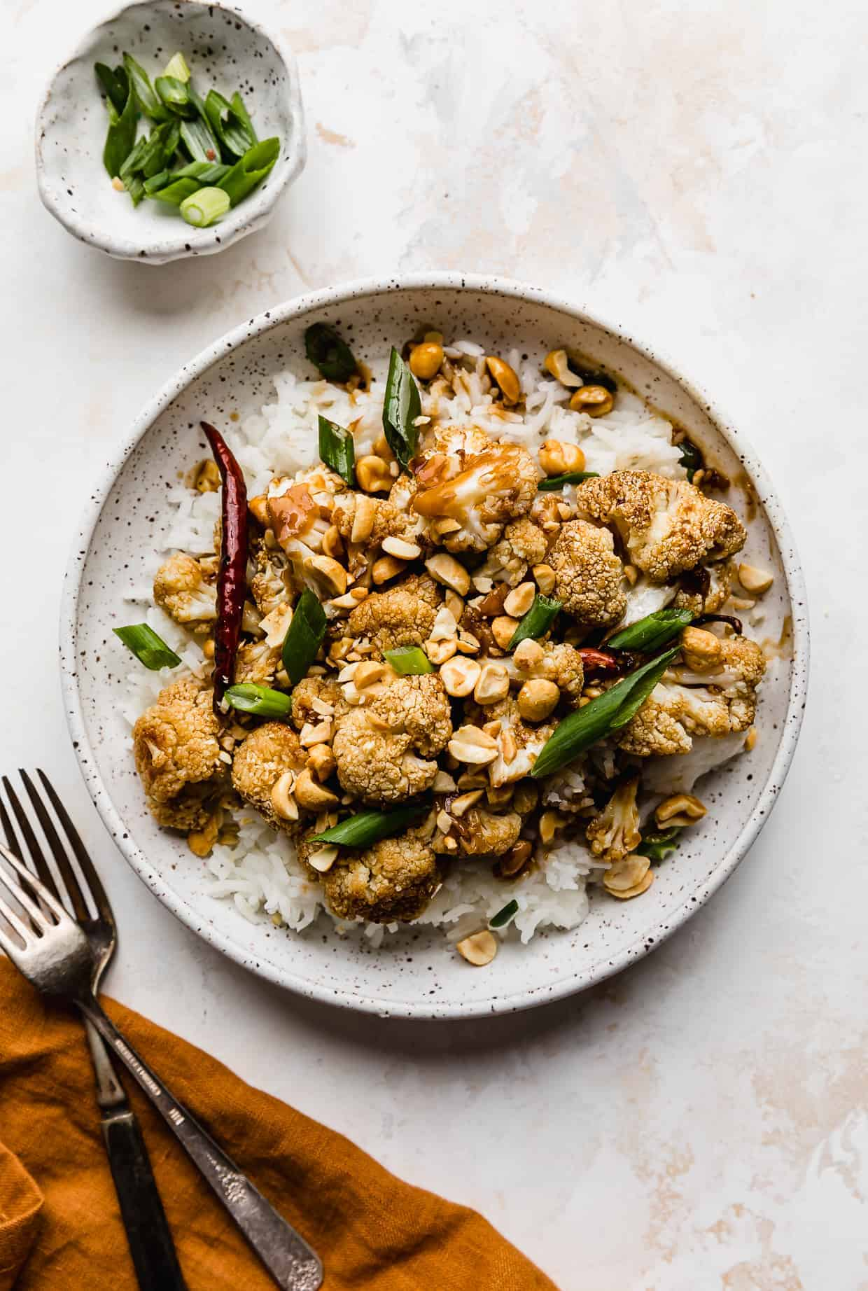 A white plate with green onion and peanut garnished Kung Pao Cauliflower, against a cream colored background.