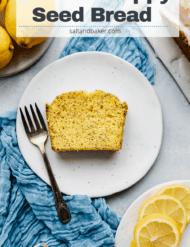 A slice of lemon poppy seed bread on a white plate resting on a light blue crinkled napkin.