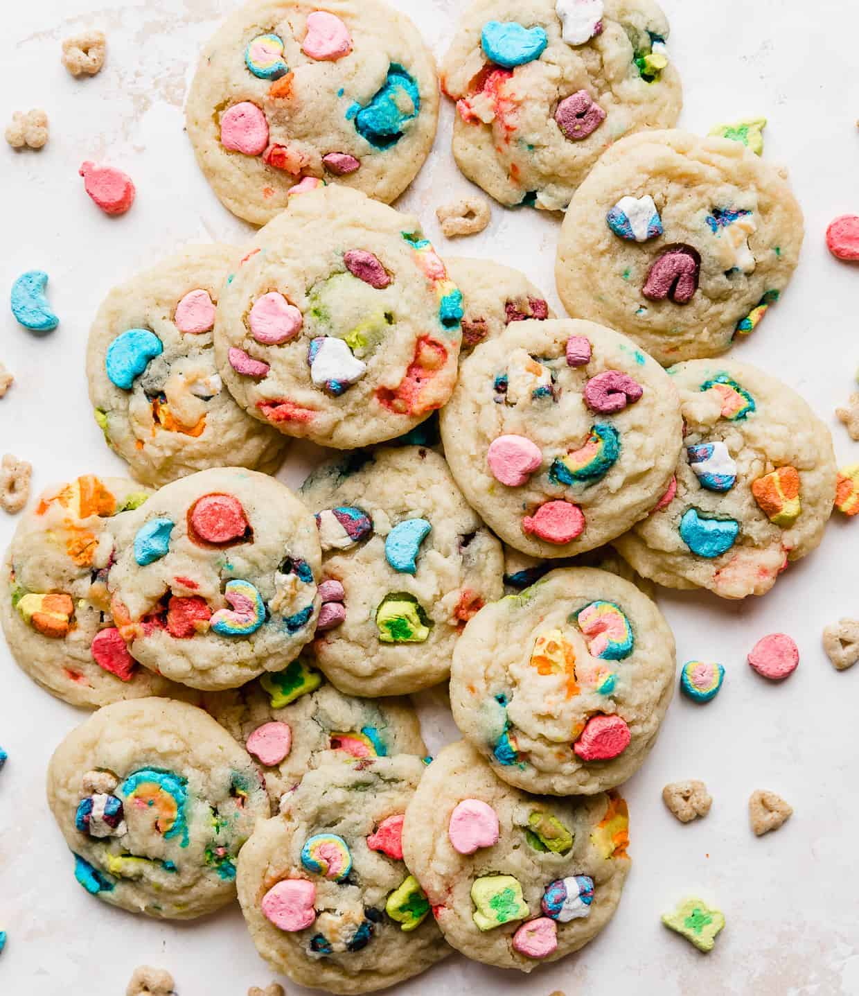 A pile of lucky charms marshmallow loaded cookies on a white background.