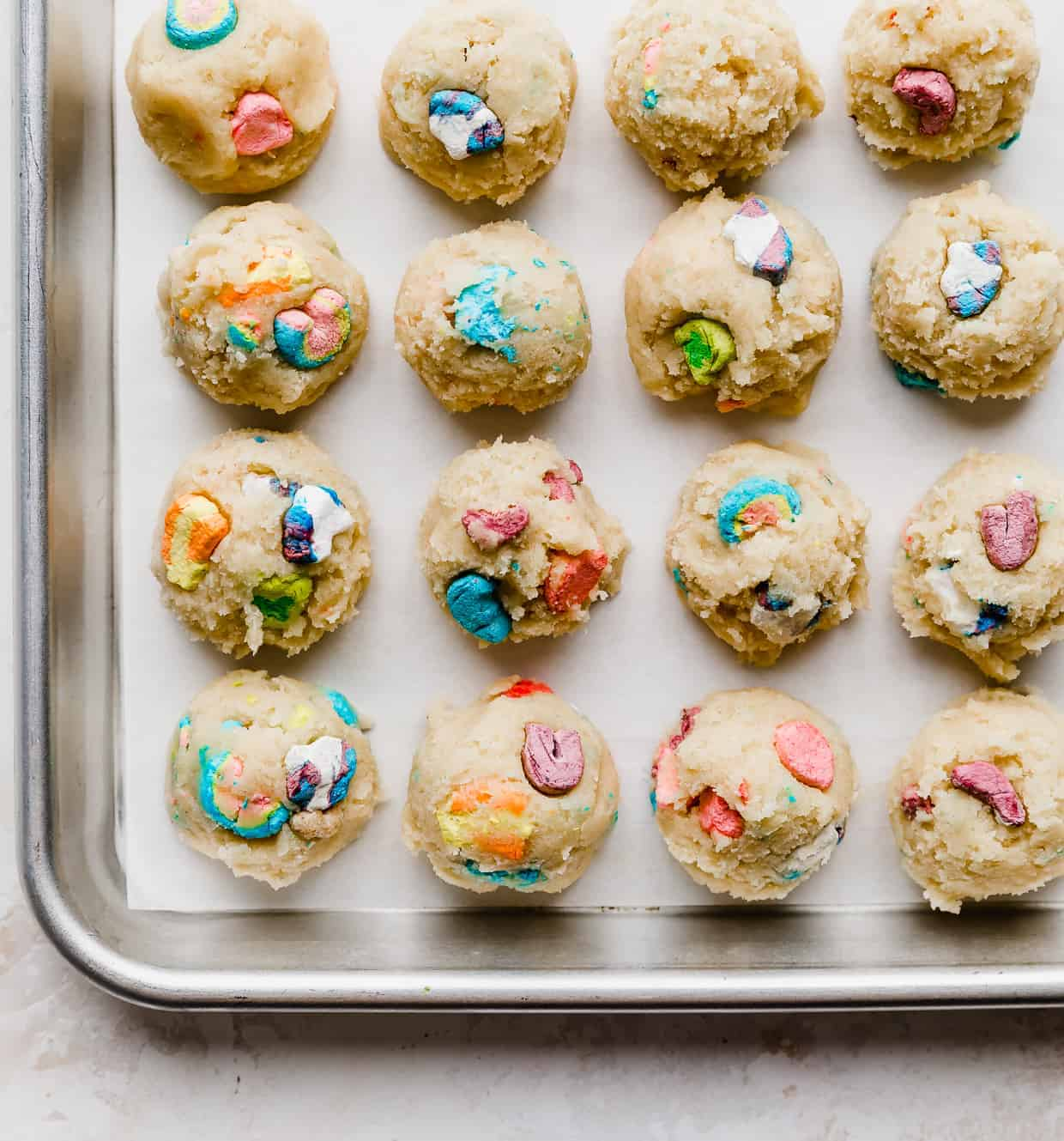 A white parchment lined baking sheet with balls of sugar cookie dough balls topped with lucky charms marshmallows on the tops.
