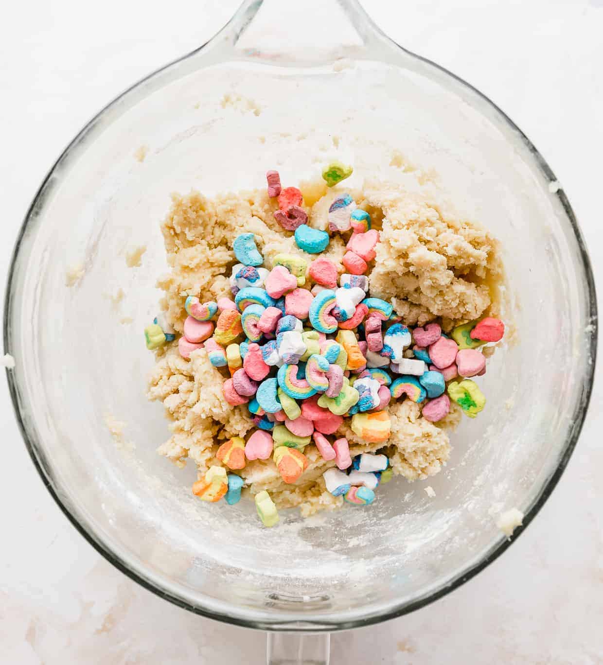 Lucky Charms cereal marshmallows in a glass bowl against a white background.