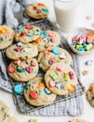 Several lucky charms marshmallow loaded sugar cookies on a wire rack against a gray napkin.