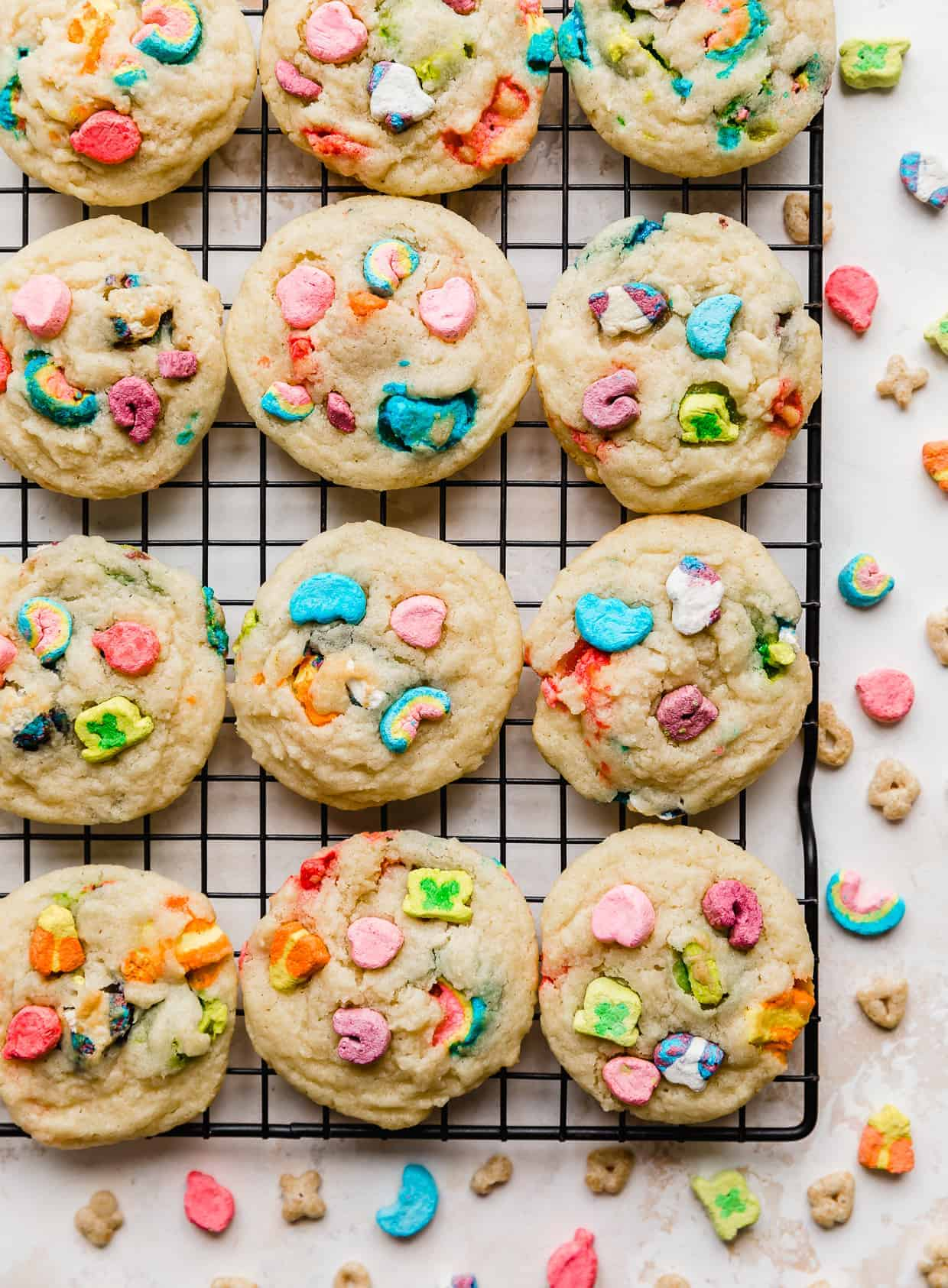 Baked sugar cookies on a black wire rack with lucky charms marshmallows baked into the cookies.
