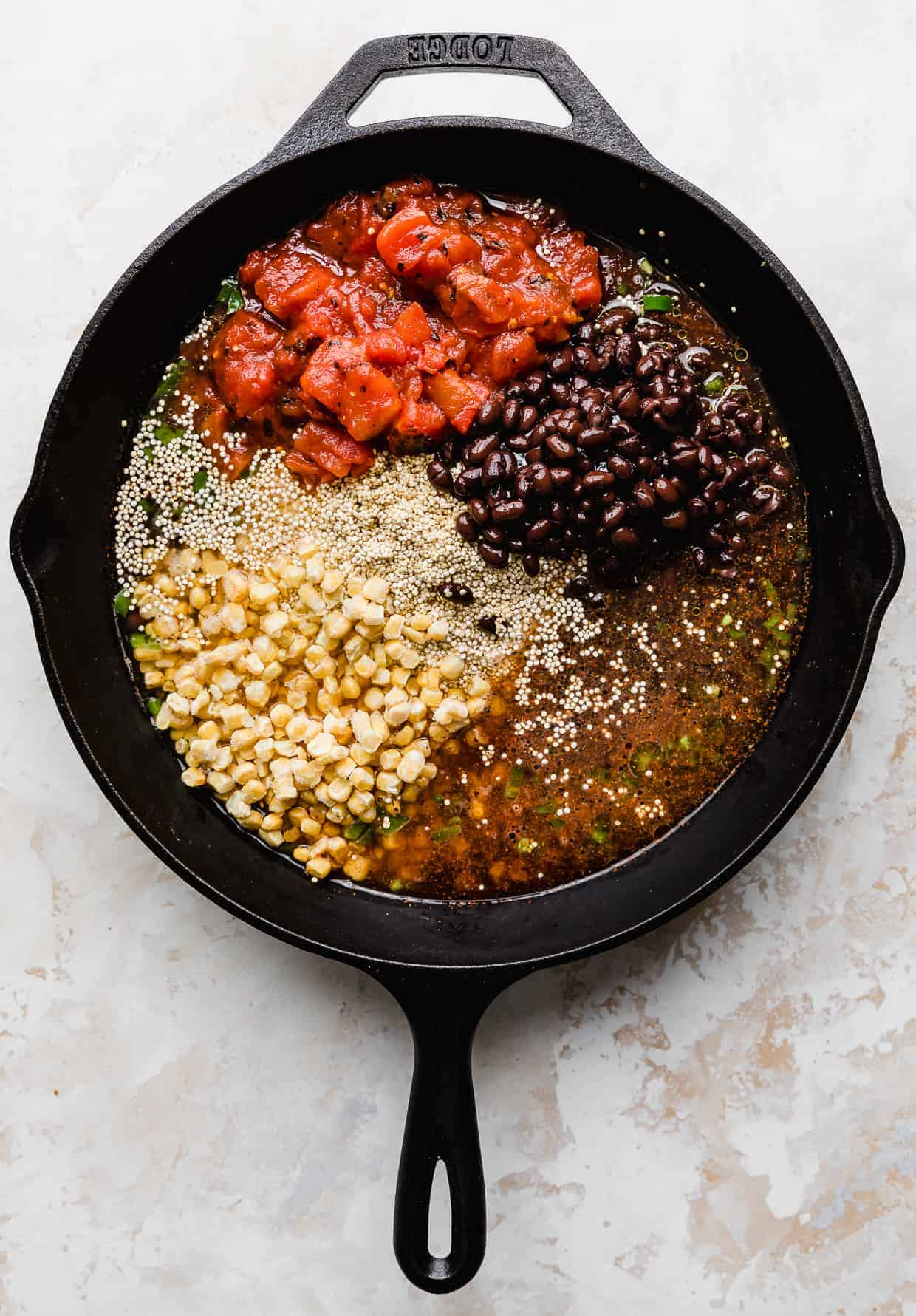 A skillet on a white background, full of uncooked quinoa, black beans, canned diced tomatoes, frozen corn kernels, and water.