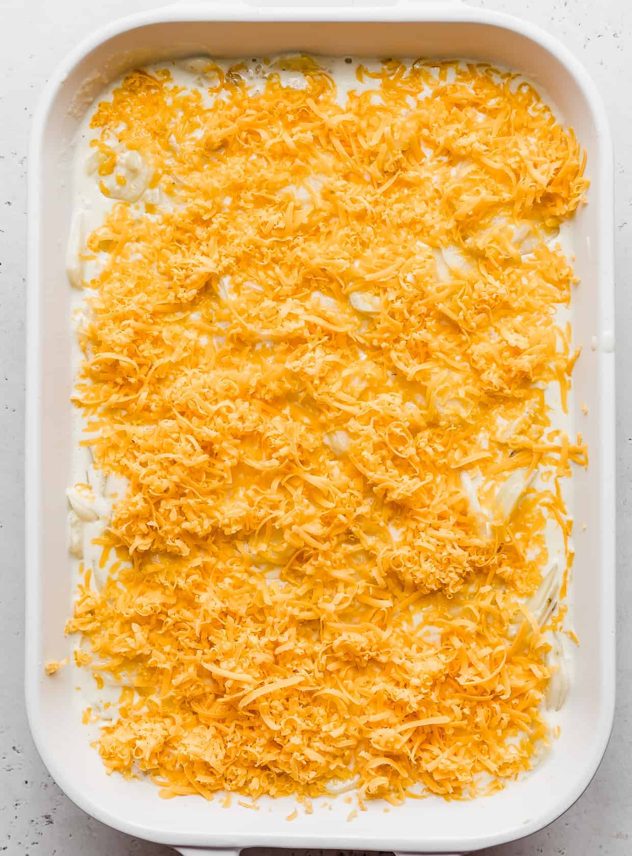 A white casserole dish topped with shredded cheddar cheese.