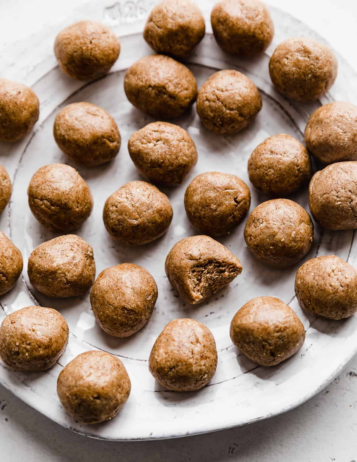 A white plate full of Snickerdoodle Energy Bites, with a bite taken out of the middle energy ball.