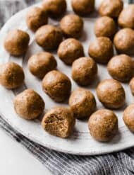 Snickerdoodle Energy Bites rolled into balls, sitting on a white plate with the closest one with a bite taken out of it.