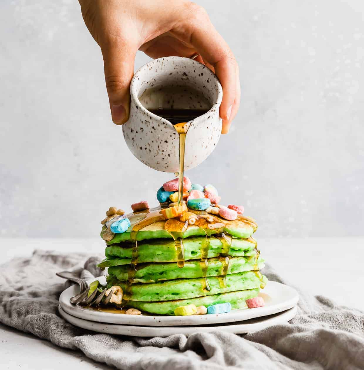 A hand pouring maple syrup over a stack of green pancakes on a white plate.