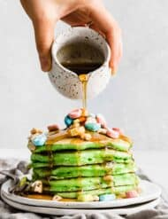 A stack of green pancakes on a plate topped with lucky charms cereal with maple syrup being poured overtop.