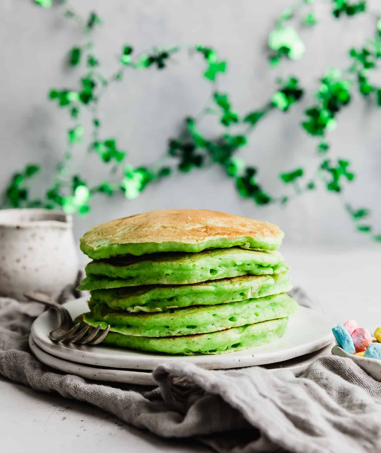 A stack of fluffy green pancakes on a white plate with green St. Patrick's day decor in the background.