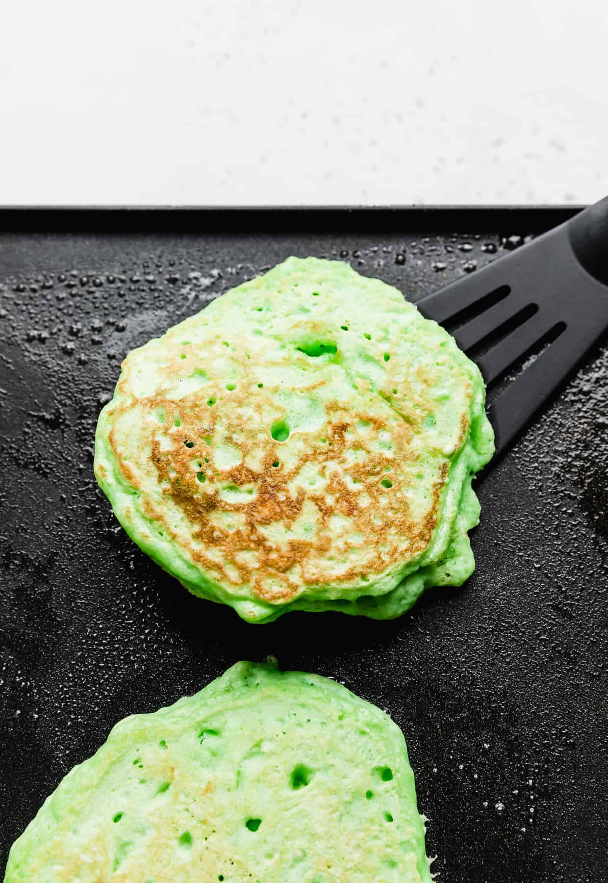 A green pancake on a black skillet with a black spatula underneath it.