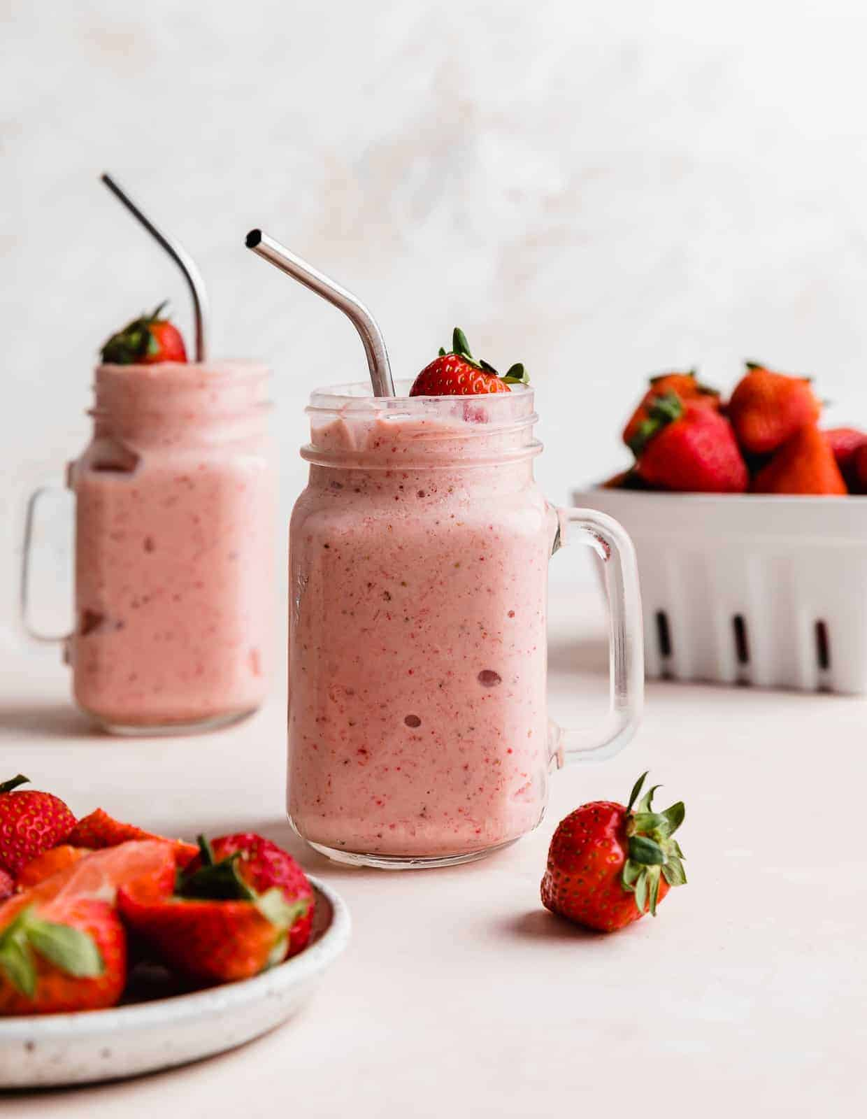 A pink Strawberry Pineapple Smoothie in a mason glass jar with a metal straw, against a white background with a basket of strawberries near the smoothie.