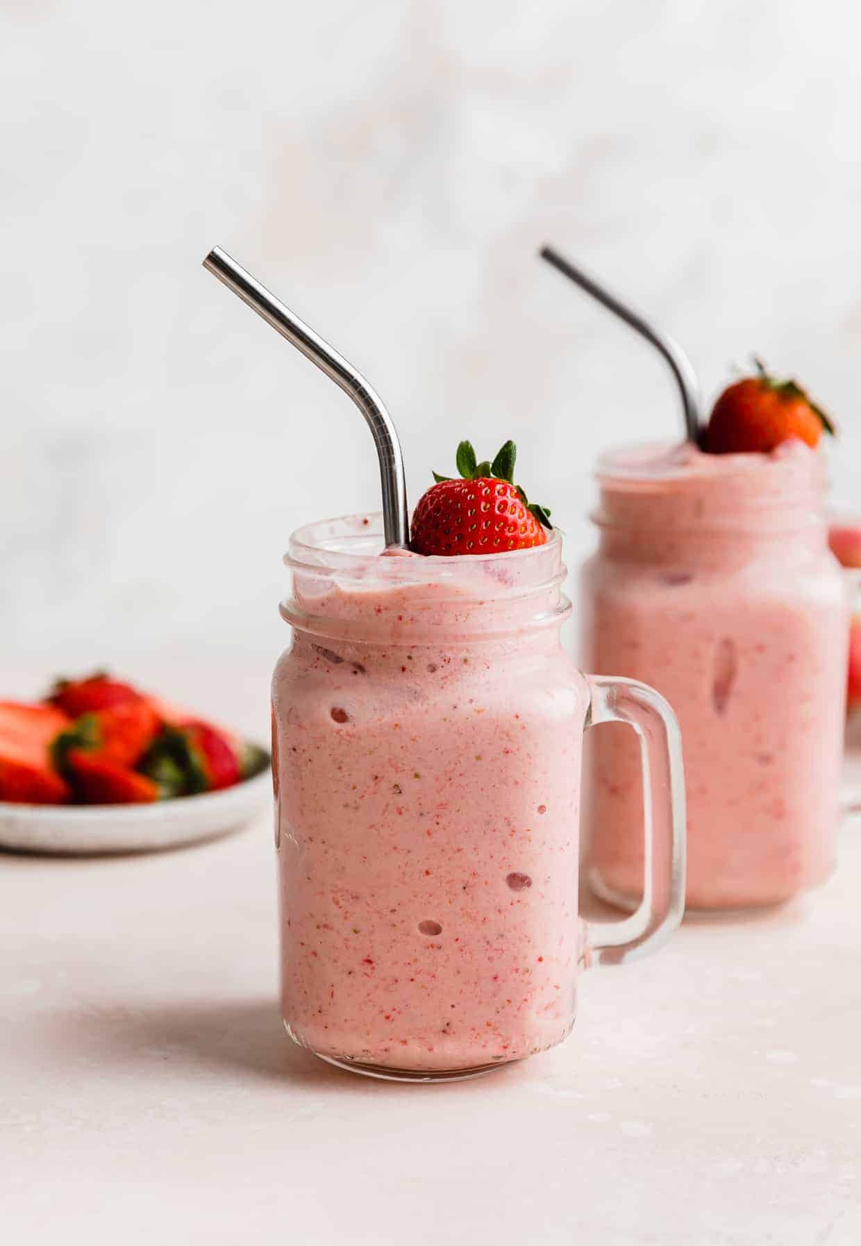 Two mason jar glasses full of Strawberry Pineapple Smoothie with a fresh strawberry resting on the top of the smoothie.