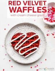 A heart shaped red velvet waffle on a white plate topped with a drizzle of white cream cheese glaze.