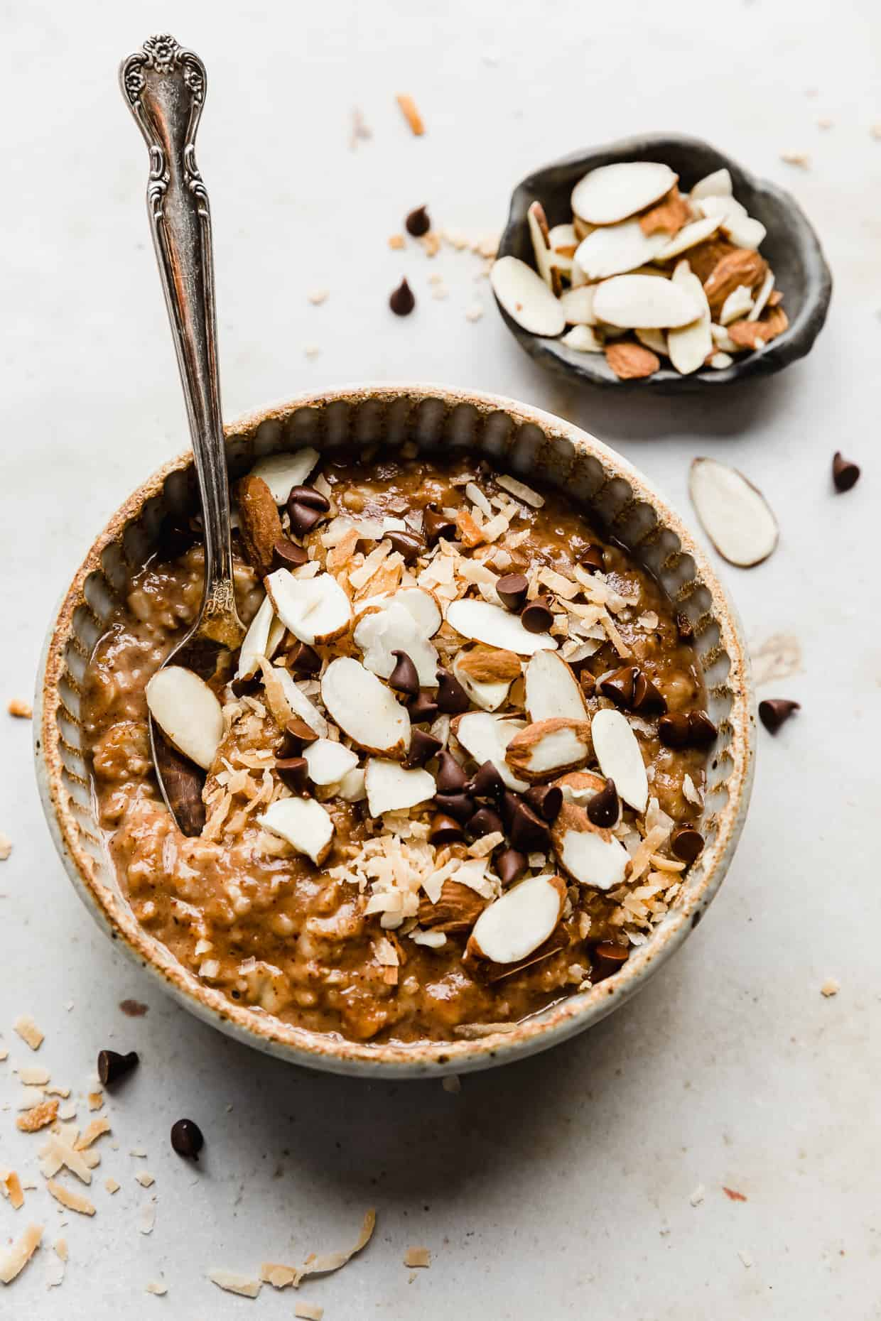 A bowl with almond joy oatmeal topped with coconut, almonds, and chocolate chips.