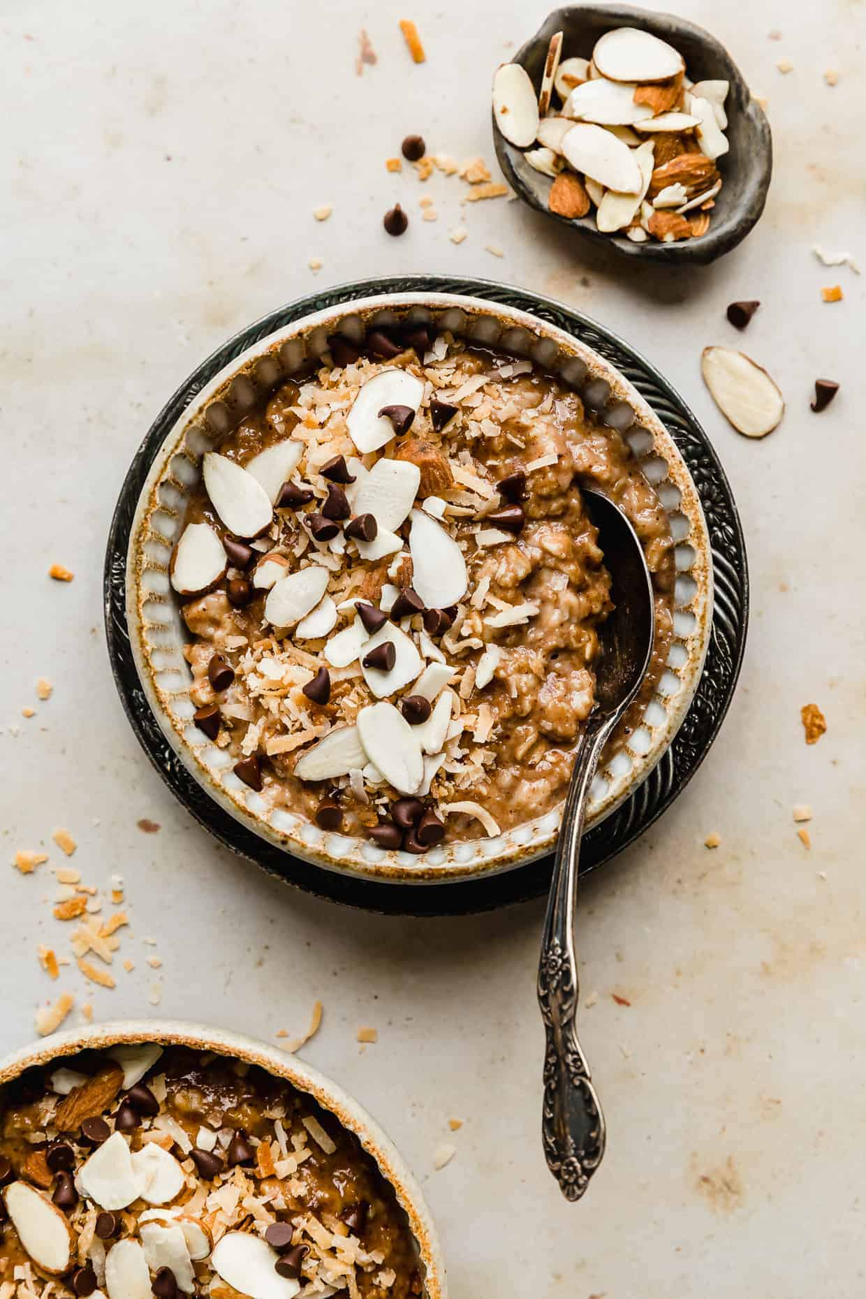 A bowl full of Almond Joy Oatmeal topped with sliced almonds, toasted coconut, and chocolate chips.