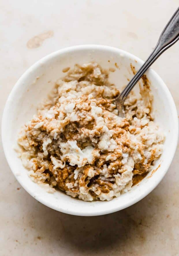 Almond butter and cooked oatmeal being stirred in a white bowl.