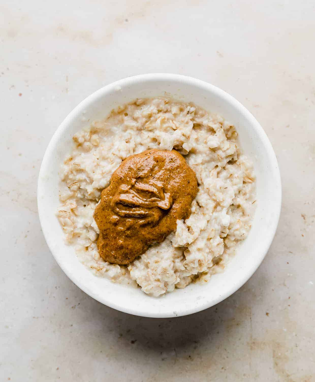 A white bowl with cooked oatmeal and a dollop of almond butter in it.