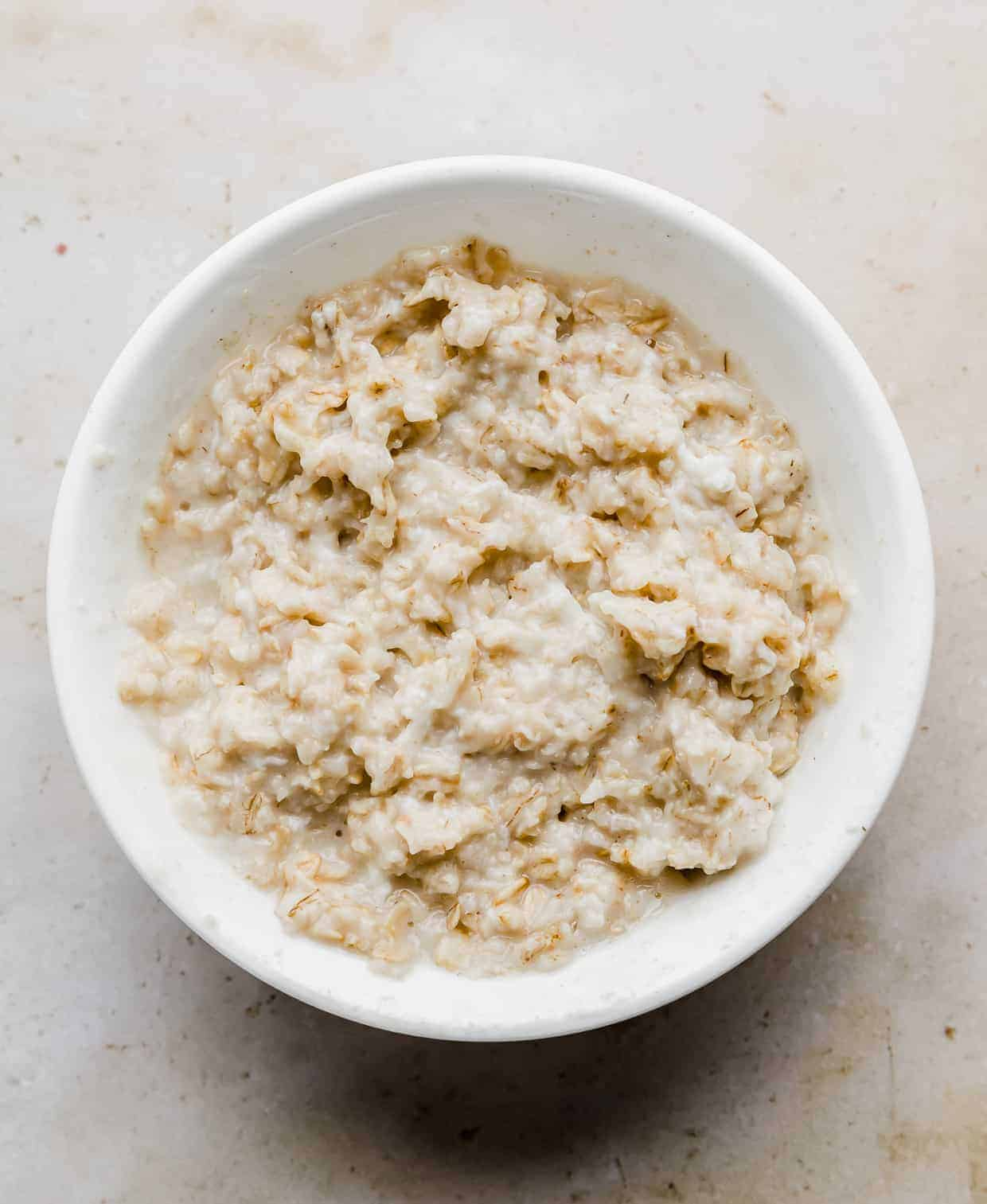 A white bowl with cooked rolled oats in it.