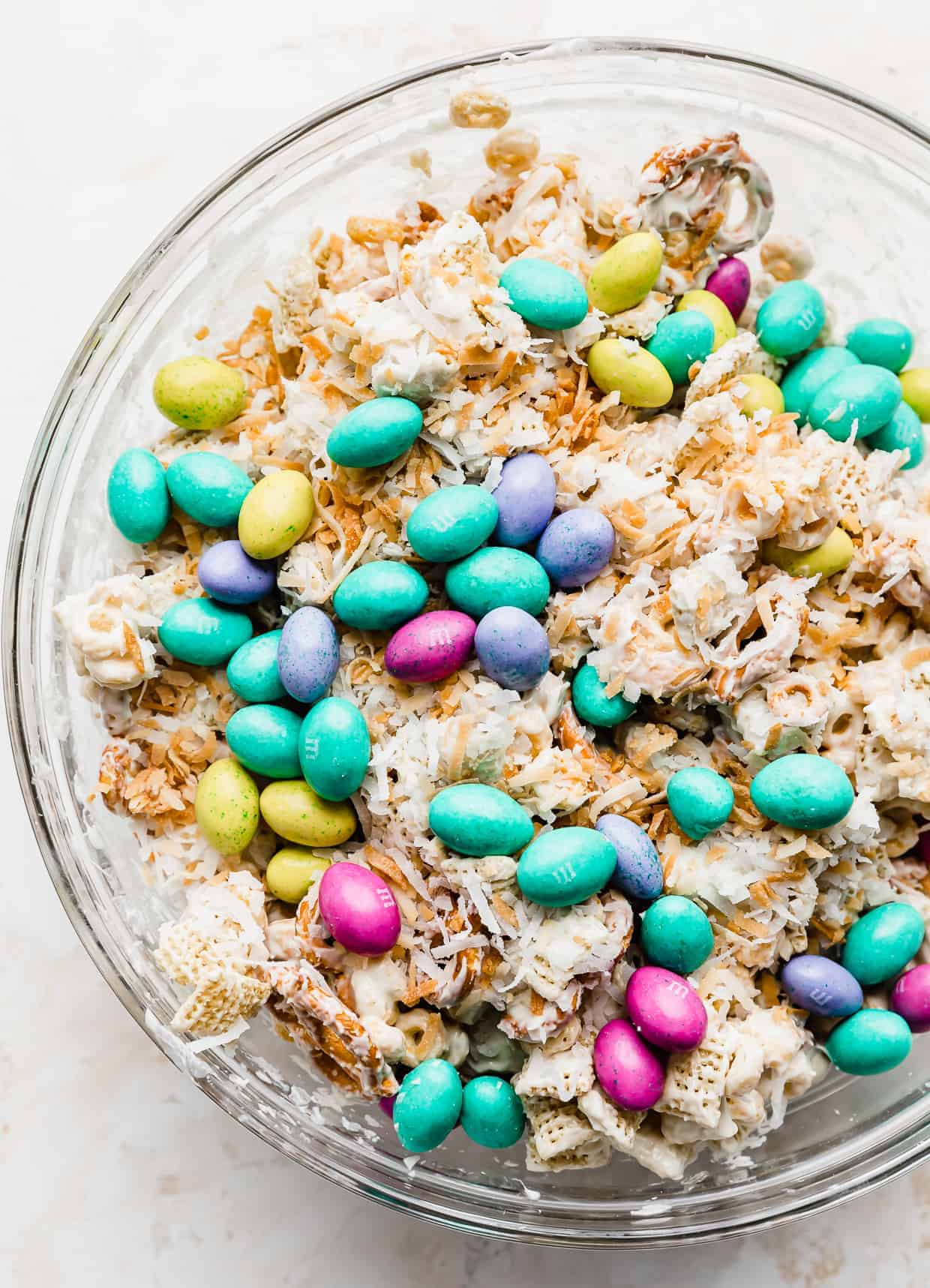 Pastel colored M&M's poured overtop a white chocolate, coconut covered cereal mix.